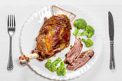 Top view lamb meat baked on a bone on a white plate with broccoli