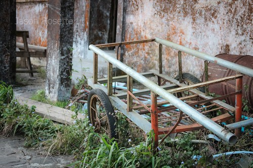 Old cart near dilapidated colonial building, Cambodia