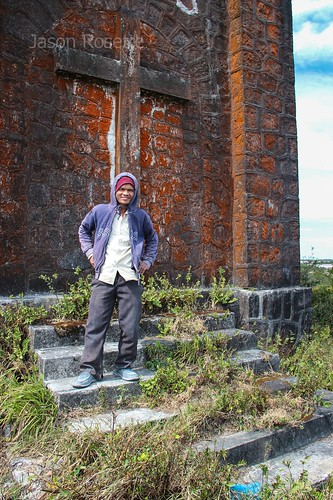 Portrait of Cambodian Worker in Front of Colonial Church on Bokor Mountain (wide-vertical)