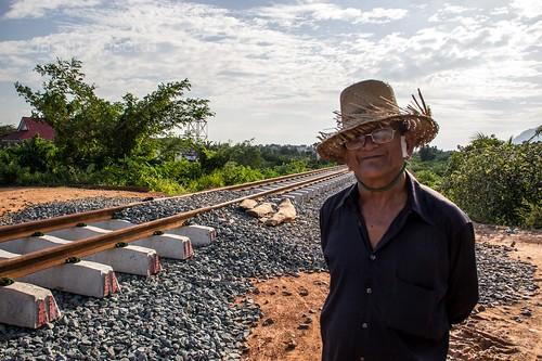 Man with Straw Hat Near Train Tracks