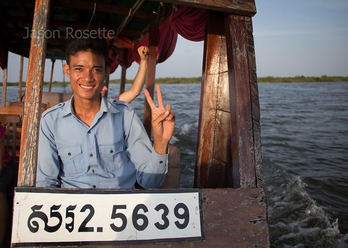 Boat Driver on Tonle Sap Lake Gives the Peace Sign