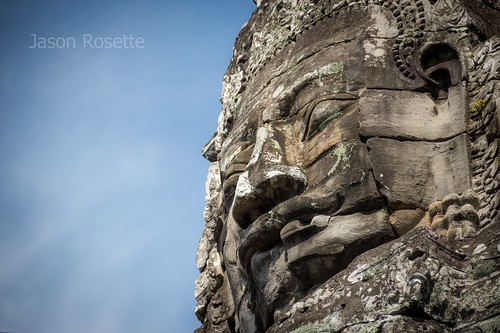 Low angle View Massive Stone Face of Angkorian King at Bayon Temple, Siem Reap