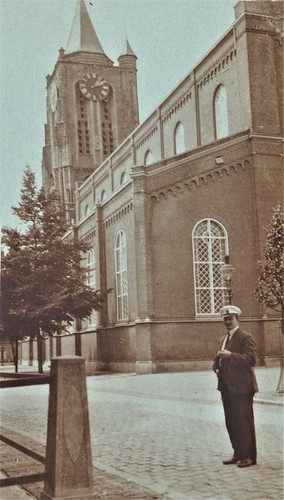 Foto - Groenmarkt, man met witte pet. Grote Kerk op de achtergrond