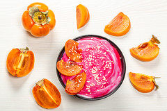 Fresh oatmeal with pink yogurt, sesame seeds and fresh persimmons on a white background. Top view