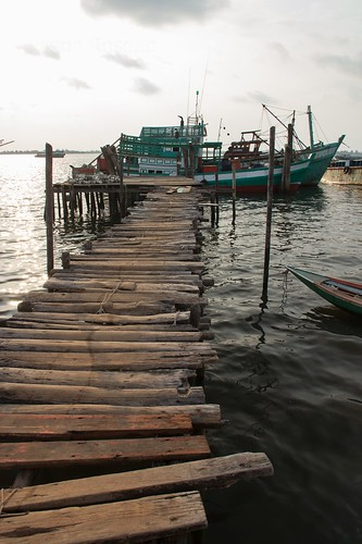 Rickety Wooden Dock with Fishing Boats