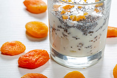 Close up of cottage cheese with yogurt and Chia seeds in a glass with dried apricots