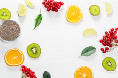 Pieces of fresh fruit, berries and green leaves with Chia seeds on a white wooden background. Top view