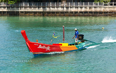 Traditional Thai Longtail Fishing boat with bright colors. Rawai beach, Phuket island, Thailand 10-10-2019
