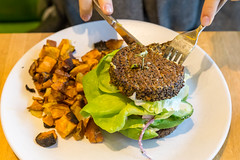 Person eating a vegan, gluten-free Inside Out Quinoa Burger (with hummus, tzatziki, organic tomato, butter lettuce, cucumber, red onion, avocado, feta) with fork and knife at the True Food Kitchen restaurant in Chicago