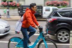 Mann in roter Jacke erkundet Downtown Chicago mit einem blauen Leihfahrrad von Divvy