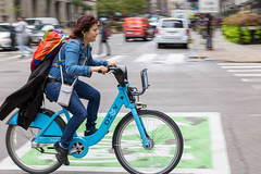 Woman with backpack and jacket attached to it rides a bicycle from the bike sharing service Divvy in the streets of Chicago