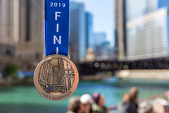 """I am a marathoner"" medal with the date ""10.13.2019"", ""Bank of America Chicago Marathon"", year and ""finisher"" written on the ribbon, and a reproduction of buildings of Chicago"