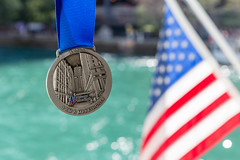 "Medal of the 2019 Chicago Marathon with ""I am a Marathoner"" written on it and a US flag and the river in the background"