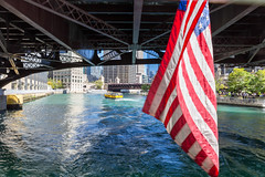 American flag hangs from a bridge over the Chicago river