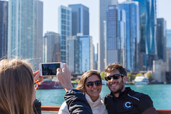 Holiday snapshot: couple poses with the Chicago skyscrapers on the background as a passer-by takes a photo with their smartphone