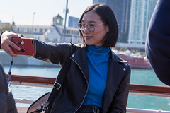 Woman wearing glasses takes a selfie during a sightseeing boat trip on the river in Downtown Chicago on a sunny day