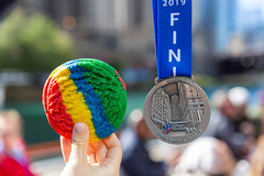 Hand shows a rainbow cookie in a slightly larger size than the Chicago Marathon 2019 finisher medal