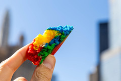 Close-up of a piece of colorful rainbow cookie held between two fingers