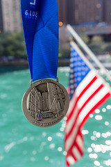 The medal given to a participant who completed the Chicago Marathon 2019, with a blue ribbon, the American flag and the Chicago River in the background