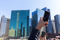 Tourists on a sightseeing boat tour on the Chicago River use their smartphones to take a photo of the 333 Wacker Drive skyscraper