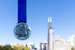 Die Chicago Marathon 2019 Medaille mit dem Willis Tower, dem 311 South Wacker Drive und dem River City Gebäude im Hintergrund