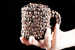 Woman holding a cup of coffee beans in her hand, black background
