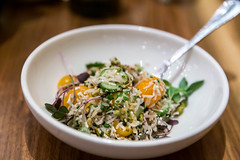 Basmati rice and beluga lentil salad with crispy shallots, yellow tomatoes, mizithra, cucumbers, pistachios and orange vinaigrette at Rotisserie Ēma in Chicago