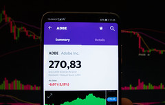 A smartphone displays the Adobe Inc. market value