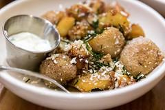 Nahaufnahme von knusprigen Kartoffeln mit Misìthra-Käse, Rosmarin und Zwiebeln-Dip bei Rotisserie Ēma in Chicago