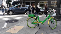 Green and yellow, Lime-E powered bike, basket, street corner, traffic, pedestrians, leaves, fall, downtown, Seattle, Washington, USA