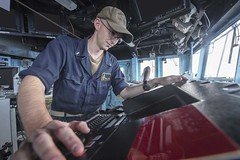 Ensign Micah Burge views a monitor in the bridge of USS Antietam (CG 54).