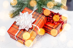 Two gift boxes with ribbons and bows on a background of snow and Golden bokeh