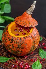Closeup of yummy pumpkin Halloween with pomegranate in fresh spinach leaves