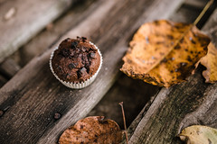A wooden background in autumn style with leaves and a muffin