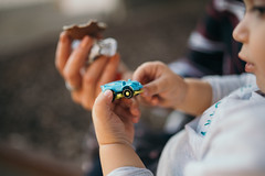 Child holding car toy from Kinder Surprise