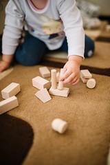 Kleinkind spielt mit Holzbausteinen und fördert dabei seine Motorik, abstraktes Denken und Kreativität