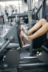 Young man using a leg press machine at the gym