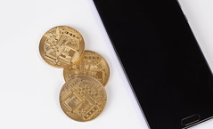 Golden coins next to smartphone on white background