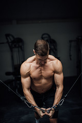 Young man doing chest exercise with cross machine