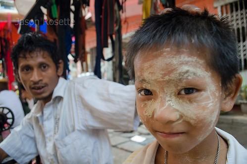 Burmese boy with belt seller in background, Rangoon (#2)