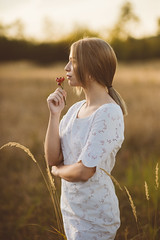 Portrait of a beautiful young woman picking flower and fruits in nature