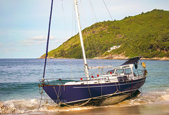 Disaster at sea. The wreck of a sailing yacht. The yacht was dropped from the anchor and thrown to the beach. Waves break the hull and fill it with water. Nai Harn Beach, Phuket, Thailand