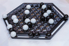 Abalone: classic board game with hexagonal board and black and white marbles on white background