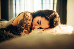Tattooed woman lying on a white bed