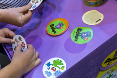 "SPIEL 19 gaming fair in Essen: the hands of two visitors playing visual perception game ""Dobble"" with animal symbols on round cards"
