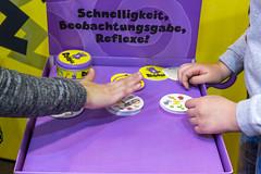 """SPIEL 19 in Essen: zwei Besucher spielen Beobachtungs- und Reaktionsspiel """"Dobble"""" mit runden Karten, die jeweils acht Symbole zeigen"""