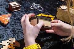 Die Rätsel Manufaktur eine Frau hält eine Truhe in den Händen