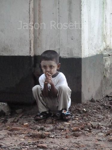 Boy in Rangon Crouches Near Building Corner (#3)
