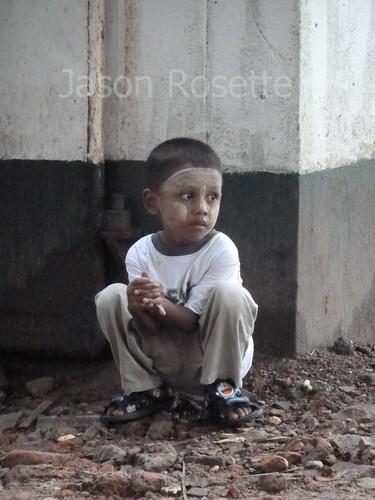 Boy in Rangon Crouches Near Building Corner (#1)