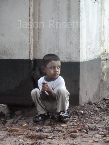 Boy in Rangon Crouches Near Building Corner (#2)